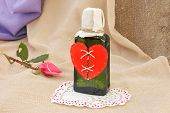 stock photo of broken heart flower  - Repaired broken red heart on a green glass bottle - JPG