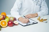 picture of clipboard  - Female nutritionist at work writing documents on a clipboard with fresh fruit on foreground - JPG