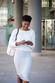 Smiling Woman Walking On Sidewalk And Sending Text Message