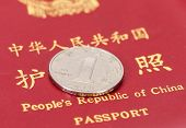 Chinese One Yuan Coin Against The Background Of The Chinese Passport
