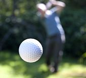 stock photo of swings  - A golf ball just coming off the tee from a golfer in swing - JPG