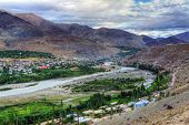stock photo of jammu kashmir  - Top view of Indus river and Kargil City valley with Himalayan mountains and blue cloudy sky in background Leh Ladakh Jammu and Kashmir India - JPG