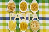 Pasta written with wooden letters on checkered cloth and uncooked pasta on porcelain spoons