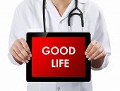 Doctor Showing Tablet With Good Life Text.