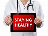 Doctor Showing Tablet With Staying Healthy Text.