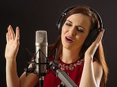 image of singing  - Photo of a beautiful woman singing into a large diaphragm microphone over dark background - JPG