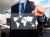 Businessman in dark suit pushing button worldmap global communication