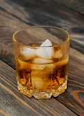 picture of scotch  - Glass with Scotch and ice on old wooden background - JPG