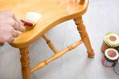 Man varnishing a chair