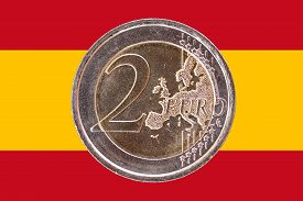 pic of spanish money  - Common face of two euros coin isolated on the national flag of Spain as background - JPG