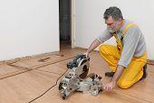 pic of laminate  - Worker cut wooden batten for laminate floor floating wood tile - JPG