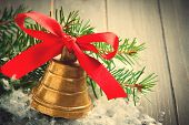 foto of christmas bells  - Christmas composition with golden bell with red satin ribbon bow and branch of christmas tree - JPG