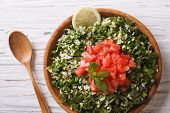 stock photo of tabouleh  - Tabbouleh salad closeup in a wooden bowl on the table - JPG