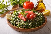 picture of tabouleh  - Arabic Salad Tabbouleh close up in a wooden bowl and ingredients. horizontal ** Note: Shallow depth of field - JPG