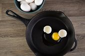 image of yoke  - Raw eggs in frying pan with yoke showing - JPG