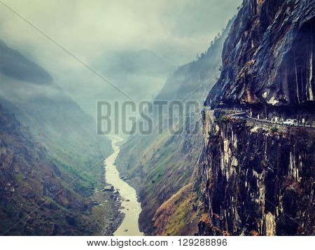 Vintage retro effect filtered hipster style image of car on dangerous road in Himalayas mountains in