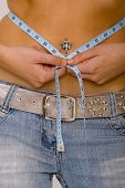 picture of pierced belly button  - close up on a young woman with a pierced belly button measuring her waistline - JPG
