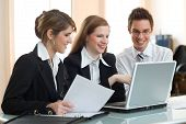 pic of business success  - three smiling businesspeople are discussing the work - JPG