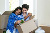 Young couple embracing while unpacking carton boxes in new house poster