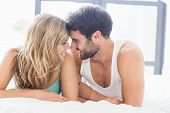 Young couple relaxing on bed face to face in the bedroom poster