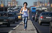 girl running on highway middle in city