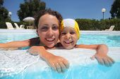 Mother with daughter in  pool to stick to hands for an edge