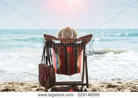 poster of Happy Woman Sitting On A Deck Chair At The Beach,relax On The Tropical Beach. Travel Concept