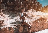 Smoking Hot Black Girl In Swimsuit Is Leaning On The Rock While Drinking Coco Water With Multiple Ca poster