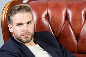 Macho Sit In Brown Leather Armchair. Man With Unshaven Face, Blond Hair, Haircut, Beauty. Barber Sal poster