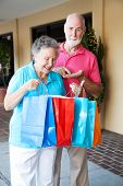 Senior couple shopping. She's happy with her purchases, and he's upset because she spent all his money.