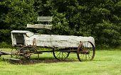 stock photo of spreader  - vintage horse drawn manure spreader sitting in a field - JPG