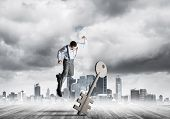 Determined Businessman Against Modern Cityscape Breaking With Fist Stone Key Figure poster