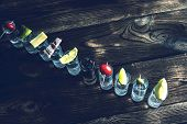 Постер, плакат: A Number Shots Of Alcohol Shots With Alcohol Top View On The Wooden Surface Over Every Shot Someth