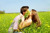 Portrait of young romantic couple embracing one another in flower field
