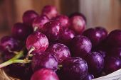 Bunches Of Purple And Red Grapes In A Wicker Basket On A Dark Background. The Harvest Of Unwashed Gr poster