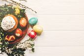 Stylish Easter Eggs And Easter Bread Cake And Flowers On Wooden Background Flat Lay. Modern Eggs Nat poster