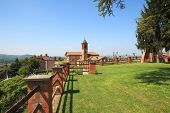 View on old church from green lawn surrounded by brick fence in Grinzane Cavour - small town in nort