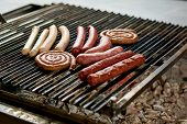 Assorted Sausages Grilling Over Coals On Barbecue. Assortment Of Different Sausages Grilling On Iron poster
