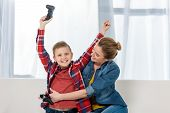 Mother Embracing Her Celebrating Son While Playing Video Games Together poster