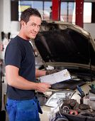 Portrait of a mechanic, looking at the camera with a service report in hand