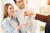 Young Couple In A Meeting With A Realtor. A Guy And A Girl Make A Contract With A Realtor About Buyi poster