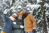 Four young affectionate friends making selfie in snowfall on winter day in the forest poster