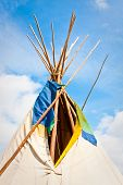 image of wigwams  - Top of a traditional wigwam against a bright blue summer sky - JPG