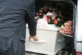 picture of funeral home  - A funeral home employee takes out a white coffin of a hearse - JPG