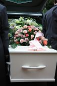 stock photo of hearse  - A white coffin covered with flowers near a hearse people taking out the coffin - JPG
