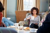 Middle Aged Woman Meeting Friends Around Table In Coffee Shop poster