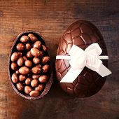 Chocolate Easter Eggs On Wooden Background With Color Ribbon Bow And Broken Egg With Chocolate Candi poster