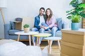 Young couple in love hugging sitting on the sofa very happy moving to a new home poster