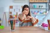 Young beautiful teacher woman wearing sweater and glasses sitting on desk at kindergarten Punching f poster