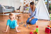 Young caucasian child playing at playschool with teacher. Playing with toy soldiers at playroom arou poster